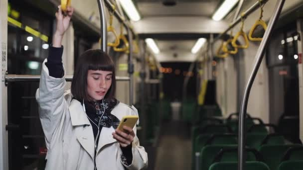 Portrait of smilling woman in headphones holds the handrail, listening to music and browsing on mobile phone in public transport. City lights background.