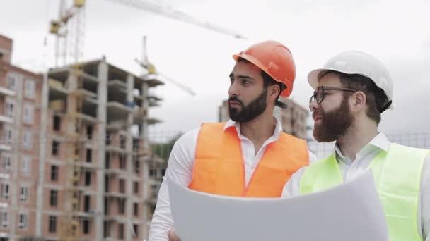 S architektem na staveništi nebo na staveništi vysoké budovy se jedná o mužský stavební rozhovor. Drží v rukou stavební výkresy.