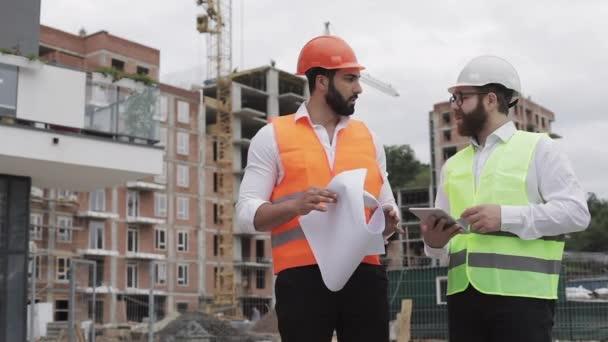 Budování obytný komplex nebo obchodní centrum. Tým inženýrů s tabletem a kreslením analyzuje plány stavební práce stavitelé.
