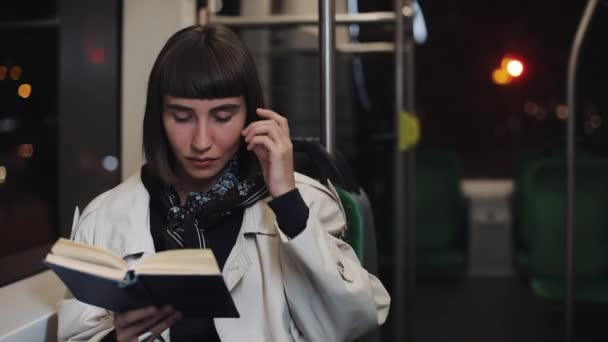 Young woman or passenger reading book sitting in public transport, steadicam shot. Slow motion. City lights background. Commuter, student, knowledge concept.