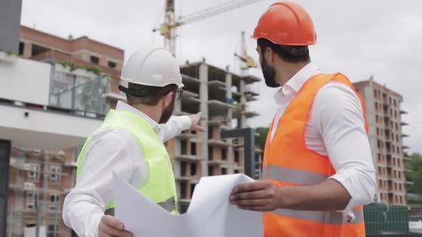 Männliche Bauingenieur Diskussion mit Architekt auf Baustelle oder Baustelle des Hochhauses. Sie halten Bauzeichnungen in der Hand.