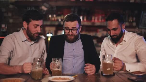 Tři staří přátelé popíjejí návrh piva a mluví ve sportovním baru. Přátelé se smějí a diskutují o novinkách v pivní hospodě.