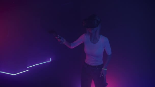 Young beautiful woman wearing virtual reality headset plays online video game with controllers. Cyber neon lighting , abstract background.