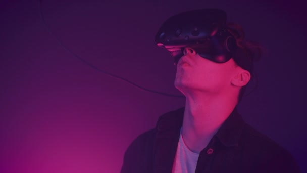 Young attractive man using modern virtual reality headset with gamepad on the neon lights background. Remote controllers, clicks, man work in VR, gesticulating by hands.