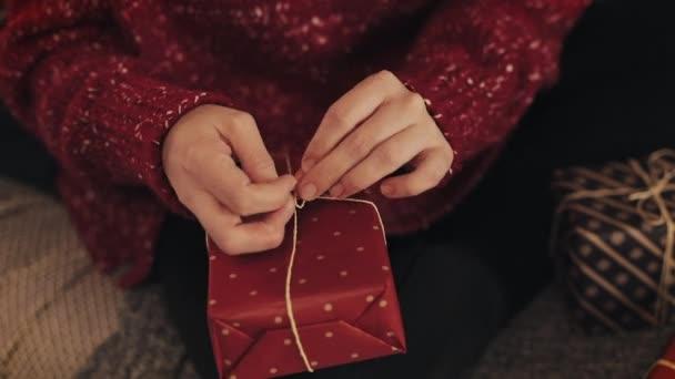 Közeli fel Womans Hands véglegesítése karácsonyi Red present Box bandaging szalag és holtversenyben a Bow fogalma ünnepek és újév.