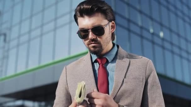 Portrait of Rich man in Stylish Suit Wearing Sunglasses Holding Roll of Money and Standing in the Street near Office Building