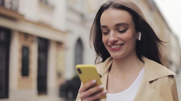 Nahaufnahme eines jungen lächelnden hübschen kaukasischen Mädchens mit Kopfhörern, das auf der Straße läuft, das Telefon in der Hand hält und tippt.
