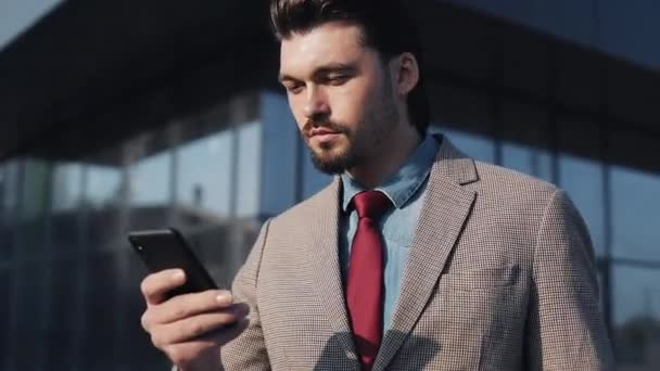 Handsome Businessman Wearing Suit and Tie Looking Amazed Scrolling the Phone and saying Wow Walking near Bussiness Building