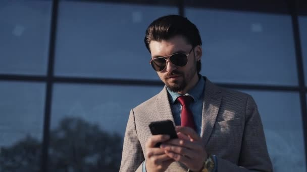 Handsome Bussinessman Wearing Sunglasses and Stylish Suit with Tie Scrolling his Smartphone Looking Satisfied in front of Office Building Portrait
