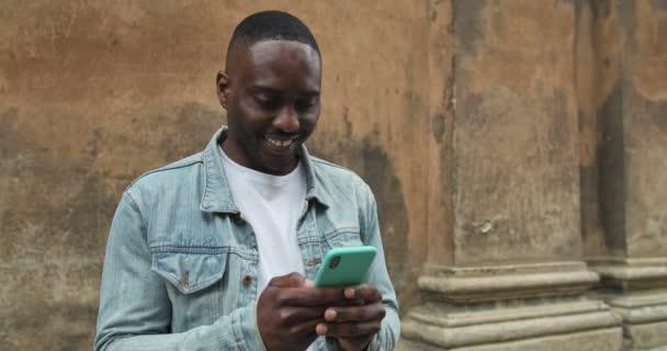 Nahaufnahme eines Afroamerikaners in Jeansjacke mit seinem Smartphone, der aufgeregt und lächelnd an der alten Hauswand steht.