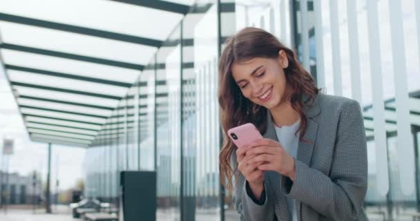 Junge attraktive Geschäftsfrau lächelnd und mit Smartphone in der Nähe moderner Bürogebäude. Schöne Mädchen in schicker Freizeitkleidung chatten in sozialen Netzwerken, während sie auf der Straße stehen.