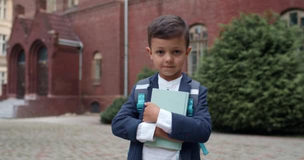 Közelről láthatja a függőséget okozó gyereket táskás könyvvel és kamerába néz. Iskolásfiú egyenruhában pózol, miközben a szabadban áll. Az oktatás és a gyermekek fogalma.
