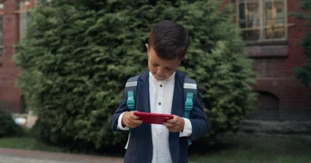 Kisfiú online játék okostelefonon, miközben séta az utcán. Egy gyerek egyenruhában, hátizsákkal a képernyőn, útban az iskolából. A szerencsejáték és a gyermekek fogalma.