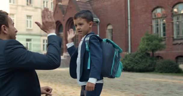 Crop kilátás apa öltönyben és aranyos fiú csinál búcsú rituálé előtt iskolába. Kölyök egyenruhában és táskás puncsos férfival, és pacsit ad, mielőtt leckéket vesz..
