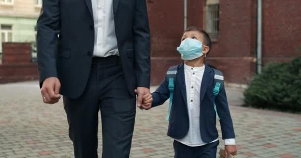 Crop kilátás férfi személy átöleli a fiát, miközben az iskolába. Kölyök fiú táska visel orvosi maszk kéz a kézben az apja séta közben.koncepció a gyermekek és az oktatás.