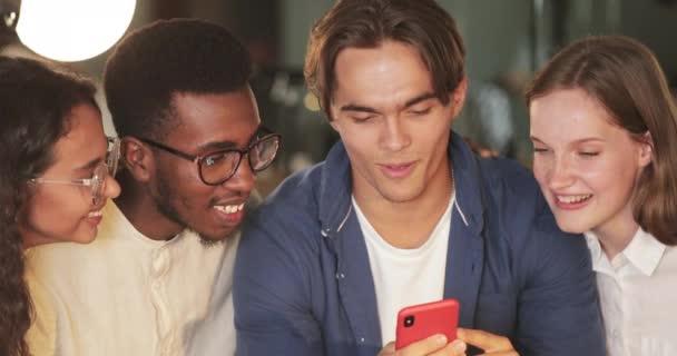 Nahaufnahme multiethnischer Menschen, die auf den Handybildschirm schauen und lachen. Junge Leute lächeln und reden, während sie lustig aussehen Foto. Konzept der Freundschaft und positiver Emotionen.