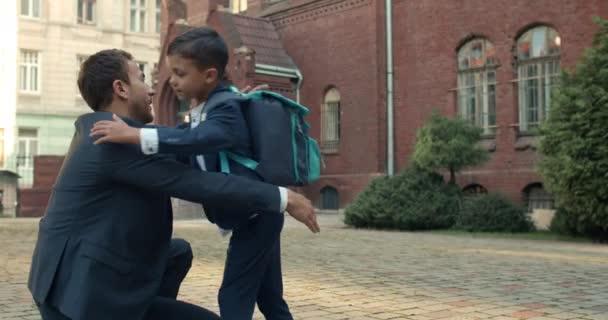 A kis vidám kölyök átöleli szerető apját és integet, miközben fut az órákon. Egy öltönyös fiatalember nézi, ahogy a fia iskolába megy. A család és az oktatás fogalma.