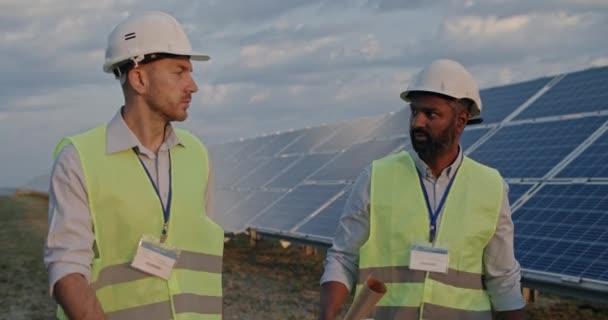 Gemischte Rasse männlicher Ingenieur mit Tablet und Schriftrollen der Ingenieurszeichnung und seinem kaukasischen Kollegen im Gespräch. Männer in Uniform und Harthelm gehen auf Solarfarm. Konzept der grünen Energie.