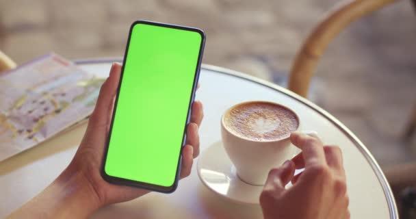 Crop kilátás a női személy gazdaság mobiltelefon és nyomja meg a zöldvászon, miközben ül az asztalnál kávéscsésze és térkép rajta. A mockup és a chroma key fogalma.