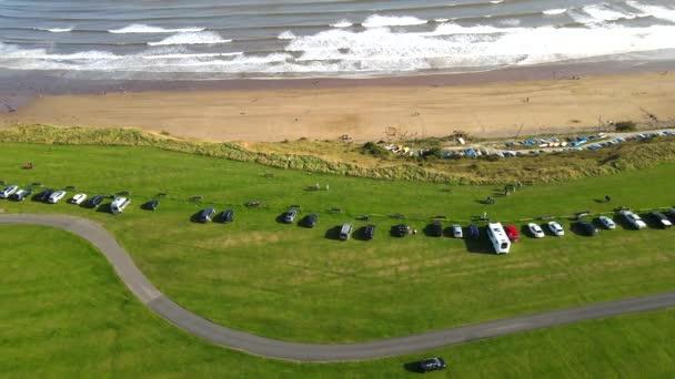 Mořské útesy na pobřeží v malé vesnici Filey v severním Yorkshiru na severovýchodě Anglie. Záběry ukazují auta a táborníky podél moře.