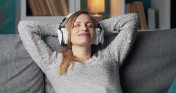 Dáma relaxuje na gauči při poslechu písní ve sluchátkách