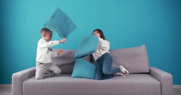 Group of two happy children fighting with pillows on couch