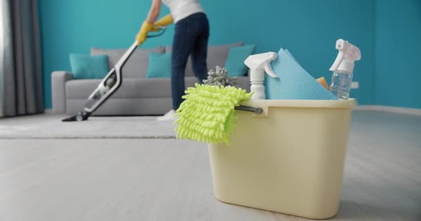 Woman using cleaning stuff while vacuuming white carpet
