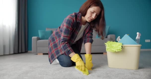 Woman in gloves standing on knees while cleaning carpet