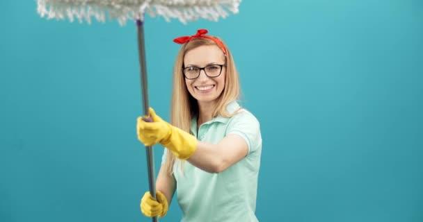 Frau mit Brille und Handschuhen amüsiert sich mit Putzmopp