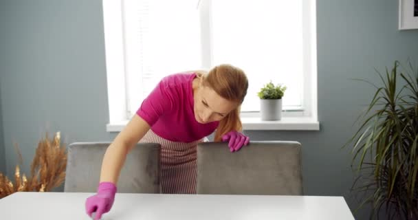 Žena v domácnosti v rukavicích úklid bílý stůl se štětcem