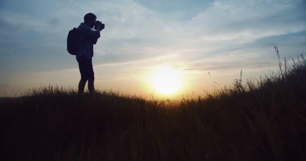 Silueta muže fotit úžasný západ slunce na kopci