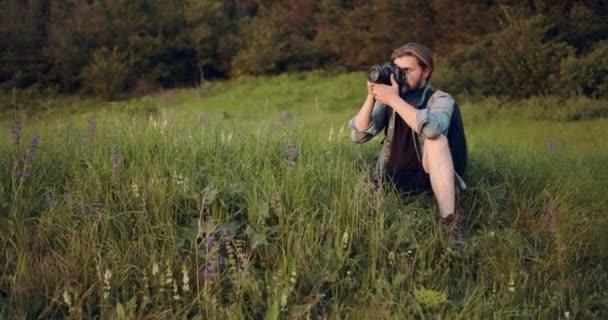 Vousatý muž sedí na zeleném kopci a používá digitální fotoaparát