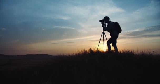 Mann fotografiert Sonnenuntergang mit Stativ und Digitalkamera