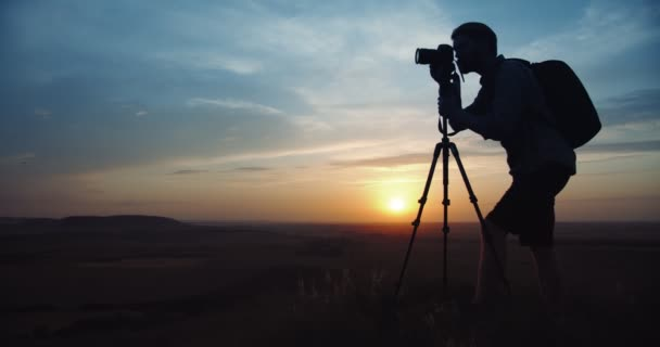 Mann in Silhouette fotografiert Sonnenuntergang mit Stativ