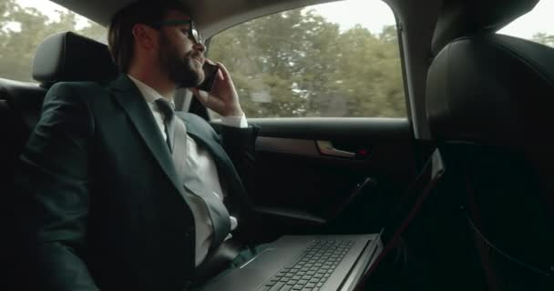 Bearded man in business suit talking on smartphone in auto