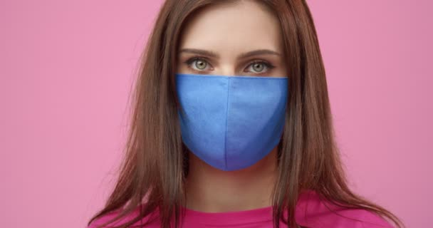 Girl posing in studio with pink background in medical mask