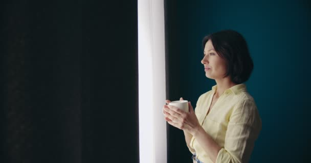 Woman standing near window and drinking morning coffee