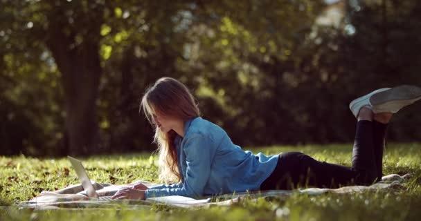 Boční pohled okouzlující blondýny studující na počítači v parku