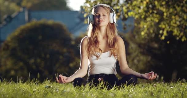 Uvolněná žena ve sluchátkách meditující o přírodě