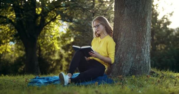 Atraktivní žena sedící na trávě a čtečka
