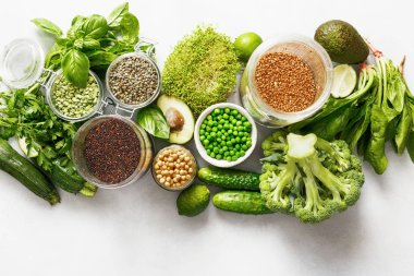 Set raw vegetables and grain products source of protein for vegetarians: cucumber, lucerne, zucchini, spinach, basil, green peas, avocado, broccoli, lime, buckwheat, green lentils, chickpea and quinoa on white concrete background, top view