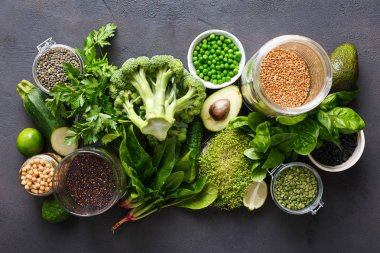 Set raw vegetables and grain products source of protein for vegetarians: cucumber, lucerne, zucchini, spinach, basil, green peas, avocado, broccoli, lime, buckwheat, green lentils, chickpea and quinoa on black background, top view
