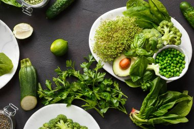 Healthy food clean eating selection source of protein for vegetarians: lucerne, spinach, basil, green peas, avocado, broccoli and green lentils on dark background, top view