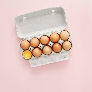 Chicken egg is half broken among other eggs in egg carton on pink background top view, flat lay