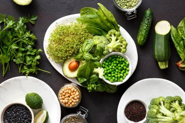 Set green vegetables and different cereals for cooking vegetarian healthy food on dark stone background top view