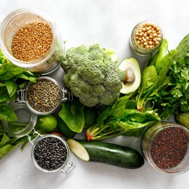 Healthy food, clean eating, selection source of protein for vegetarians: cucumber, lucerne, zucchini, spinach, basil, avocado, lime buckwheat, black beans, black quinoa, chickpeas, green lentils on gray concrete background, top view.