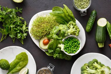 Set healthy food for cooking clean eating source of protein for vegetarian: cucumber, lucerne, zucchini, spinach, basil, green peas, avocado, broccoli, lime and green lentils on dark background, top view