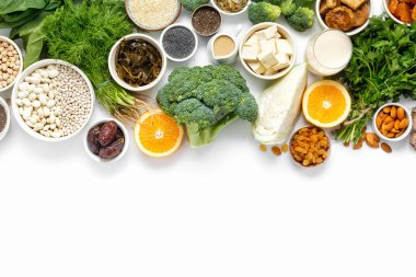 Source of calcium for vegetarians. Top view healthy food clean eating: fruit, vegetable, seeds, superfood, leaf vegetable on white background with copy space
