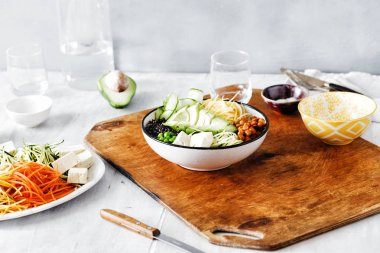 Vegetarian buddha bowl. Clean healthy food concept. Spiralized vegetables, avocado, green peas, cucumber, chickpeas and black quinoa on white wooden table