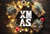 Weihnachten Hintergrund. Wort Xmas und Kranz aus Weihnachtsdeko und Weihnachtsbeleuchtung auf dunklem Holz Draufsicht flach zu legen